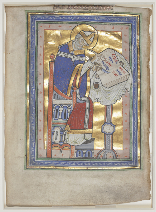 An image from a medieval manuscript, which depicts a robed man sitting at a desk, writing with a quill pen and a knife