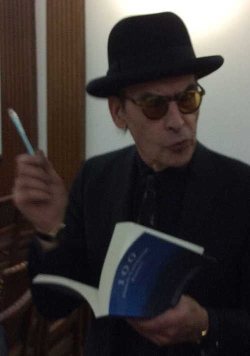 Photograph of Jules Deelder wearing a black hat with a book and pen in his hand