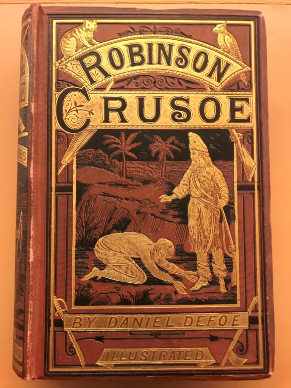 Book binding showing Friday at the feet of  Robinson Crusoe