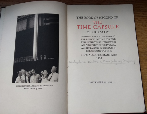 The title page of the Time Capsule Record - opposite is a black and white photograph of a group of men in shirts and ties watching the capsule being lowered into the ground.