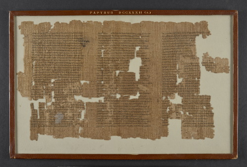 A fragmentary piece of parchment with columns of Greek writing in a frame