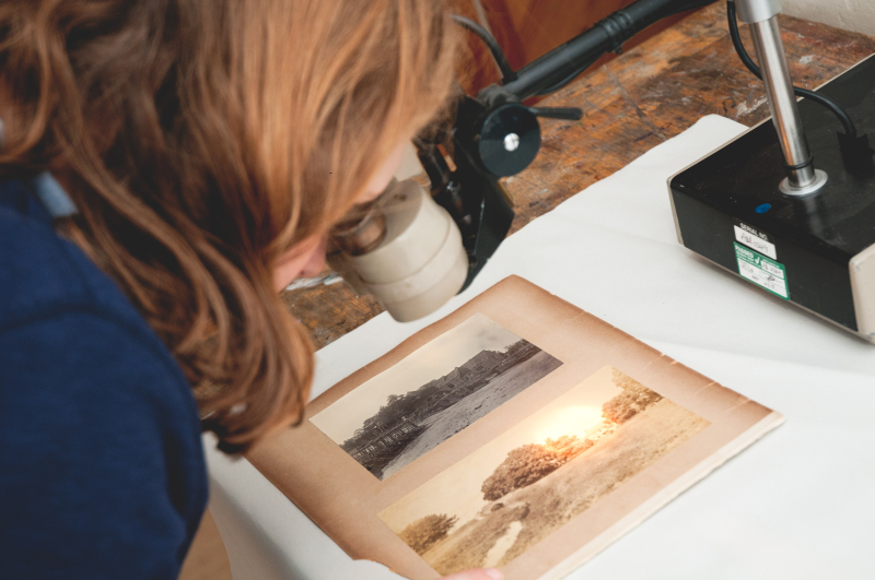 A woman inspects two historic photographs using a microscope.