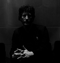 Black and white image of Neil Gaiman; his hands are extremely prominent while the rest of his face and image are quite dark