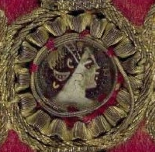 A close up featuring a figure's head in profile surrounded by a circular frame of gold thread against a red background.