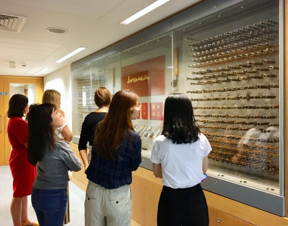 Group of British Library placement students looking at a display of bookbinding tools.