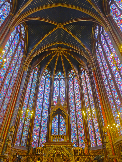 Interior view of Sainte-Chapelle, a magnificent gothic chapel with very high windows featuring geometric stained glass.