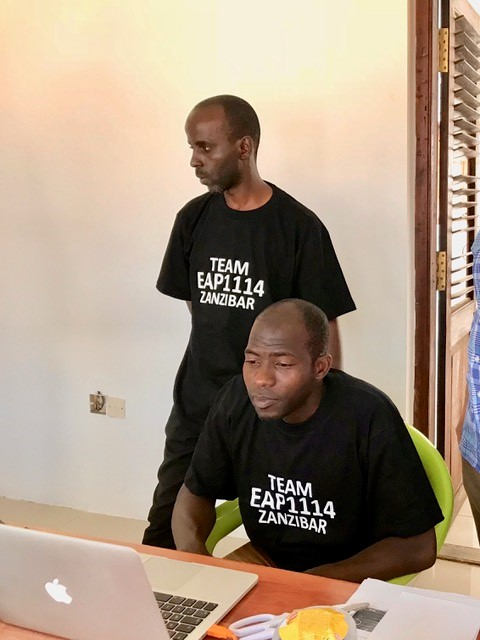 Two team members wearing Team EAP1114 Zanzibar T Shirts  looking at a laptop