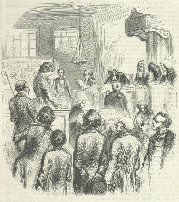 Girl standing in dock in court room