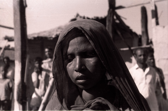 Close up of a woman with the refugee camp in the background