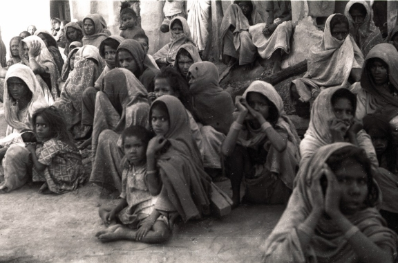 Group of women and children sitting huddled together and looking at the camera