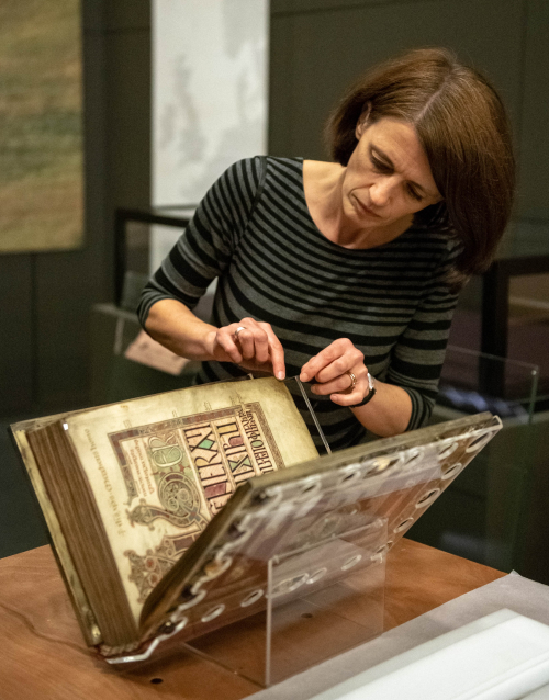 Claire Breay handling the Lindisfarne Gospels prior to its installation in the Anglo-Saxon Kingdoms exhibition.