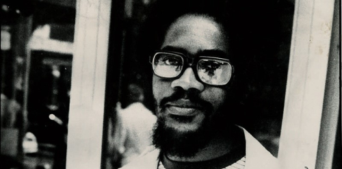 Black and white photo of Walter Rodney standing in front of a door or window