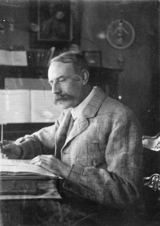 Photograph of Edward Elgar composing music at his desk