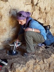 An image of a woman archaeologist using a piece of equipment to determine material composition