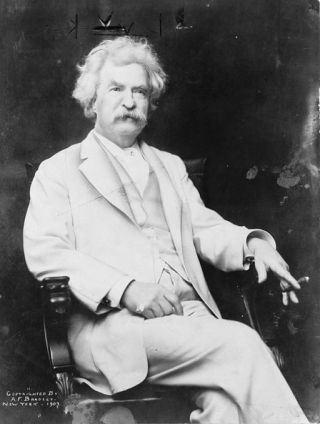 Photo of Mark Twain seated with cigar in hand