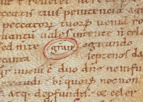 A hole in the parchment, through which the word 'gratiam' ('grace') is visible