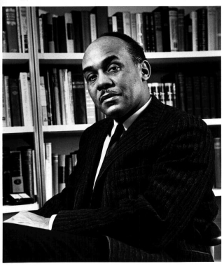 Black and white photo of author Ralph Ellison in front of bookcase