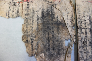 A close-up of a water damaged page.The text is smudged and a darkened tideline is visible.