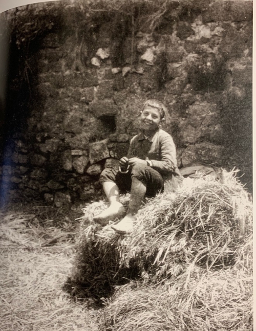 Photograph of a shepherd boy sitting on a heap of straw