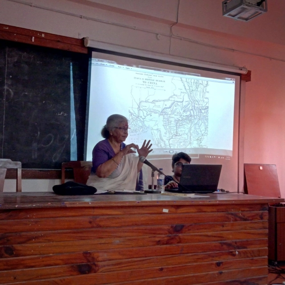 A woman presenting at the workshop a slide of a map is in the background