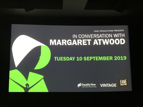 Screen from In Conversation with Margaret Atwood, Tuesday 10 Sept 2019, showing the lead image from the book's cover - a handmaid dressed in green