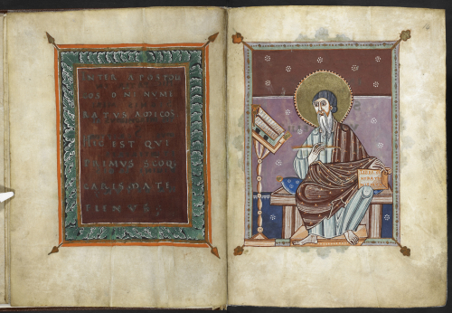 An opening in the Cologne Gospels. On the left page is a frame containing silver writing on a purple background; on the right page is a picture of a seated man with a beard, long robe and large halo, holding a pen and a book, looking at an open book on a stand.