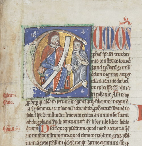 Large decorated initial C on a blue, square background, within which are two male human figures. The man on the left is seated, bearded and holding a scroll, and the other person is standing to his left and facing him.
