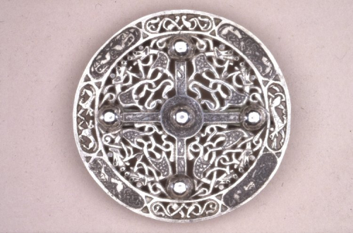 An Anglo-Saxon silver disc brooch, decorated with animal and foliage motifs and a cross design