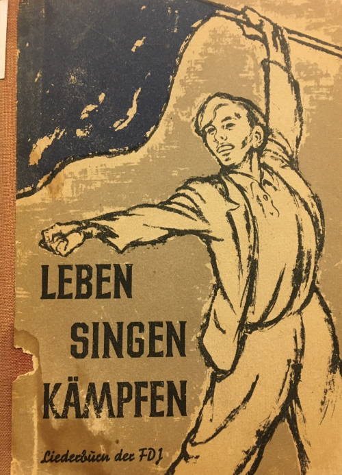 Cover of songbook 'Leben, singen, kämpfen' showing a young man brandishing a flag