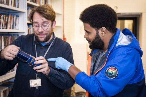 Image of AWATE chatting with Jowan from the British Library's Acquisitions and Cataloguing team, while inspecting wax cylinders that 100 years old.