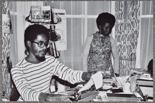 Black and white photo of Walter Rodney sitting at a typewriter on a table covered with papers; a woman stands behind him