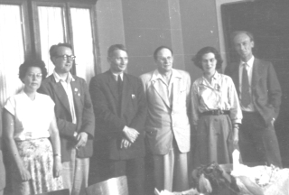 A black and white photograph of four men and two women in a room.