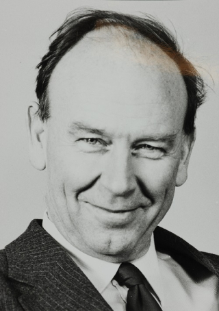 A head-and-shoulders shot of a grinning, balding white man in a suit and tie