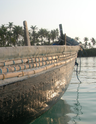A close-up of a wooden boat on water, with an area of calm water immediately around it contracting with the rippling water further away