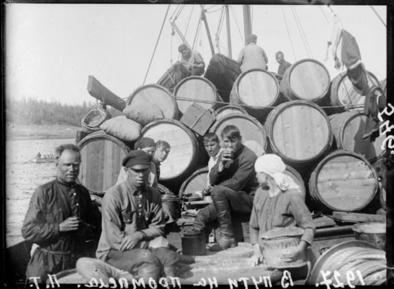 Boat stacked with many barrels. Several man look at the camera.