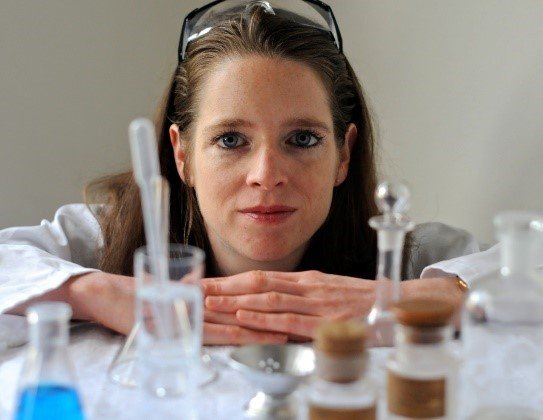 An image of Dr Rachel Edwards-Stuart behind some flasks