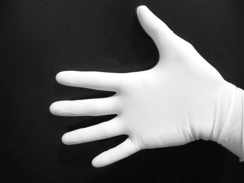 A photo of a hand wearing white gloves