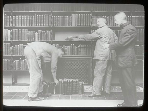 Three men dusting books