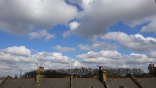 A photograph of a sky filled with fluffy cumulus clouds over the roofs of suburban houses