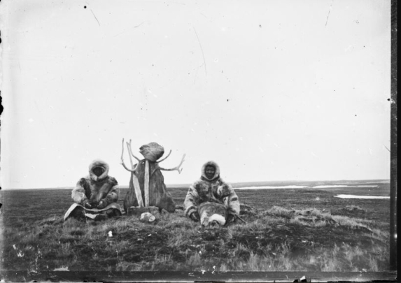 Two men dressed in fur sitting either side of a ritual site