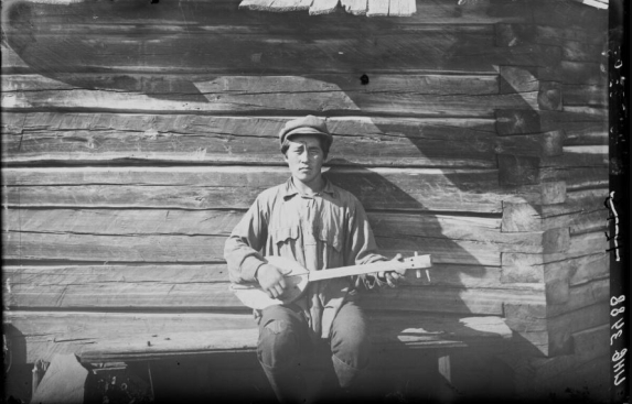 Man sitting by a log cabin and playing a stringed instrument