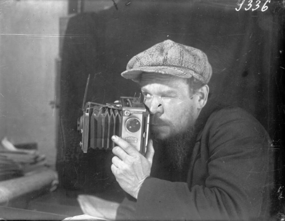 Close up of a man wearing a cap and looking through a camera viewer