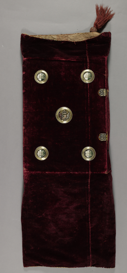 A chemise binding for a 16th-century manuscript, made of burgundy velvet, with five painted enamel badges pinned its covers and a small tassel attached to its top left-hand corner.