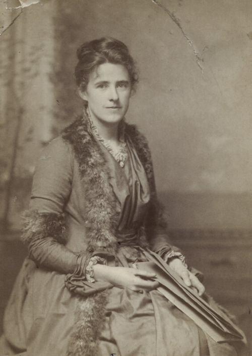 Black and white portrait of Maria wearing an elegant dress with fur trims, sitting on a chair, facing forward and holding her papers