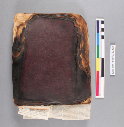 Charlotte Canning's burnt diary showing a darkened binding and missing edges. F699 2/2/2/3 before treatment