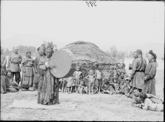 A group of people watching a shaman beating a drum