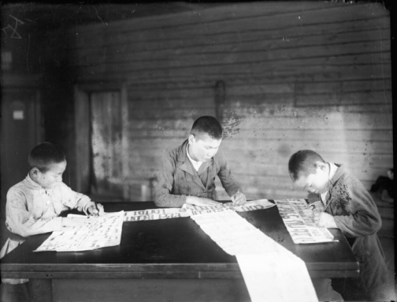 Three boys around a large table doing school work