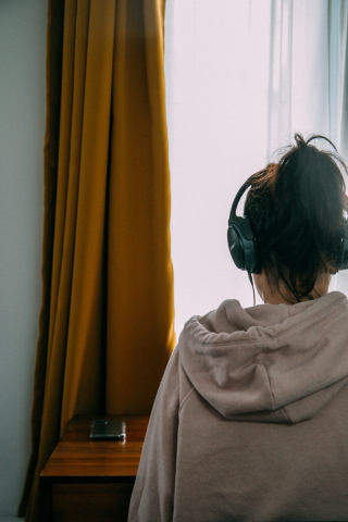 Photo of woman wearing headphones sitting at desk by Charles Deluvio on Unsplash