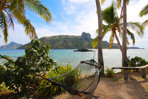 Hammock tied between two trees near a beach on a tropical island.