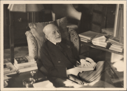 Black and white portrait of Bernard Berenson in his study at Villa I Tatti surrounded by a few his books